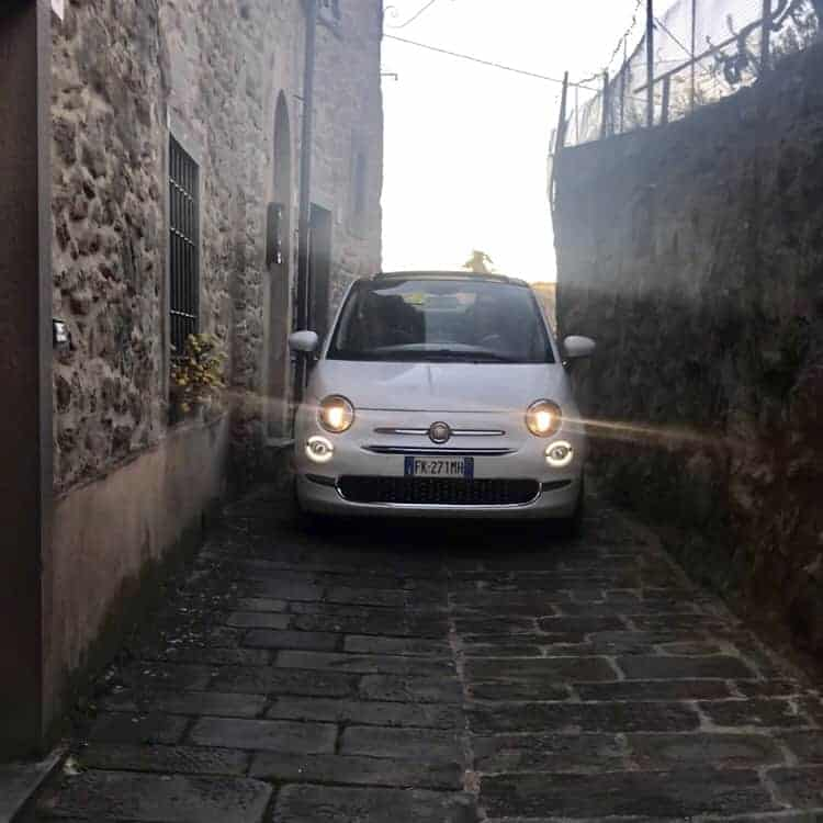 Fiat 500 creeping through a hilltop town in Italy